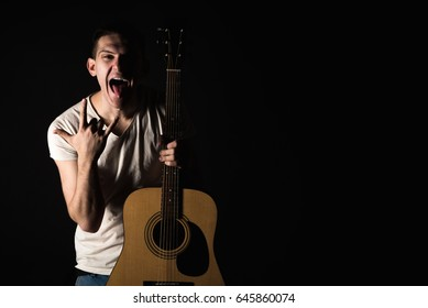 Guitarist, music. A young man stands with an acoustic guitar and shows his tongue and fingers on a black isolated background