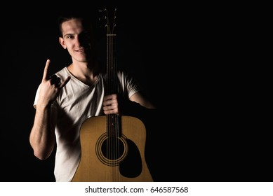Guitarist, music. A young man stands with an acoustic guitar and shows his fingers, on a black isolated background