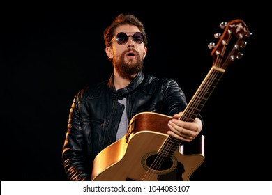 guitarist on a dark background, glasses