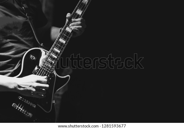 Guitarist on stage for background, soft and blur concept. Close up hand playing guitar. young musician playing guitar, live music background.Band performs on stage, rock music concert.