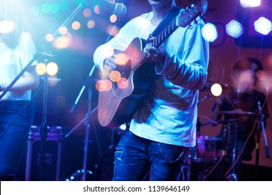 Guitarist on stage with lighting for background. Guitar player, soft and blur concept.