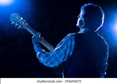 guitarist on stage playing guitar under blue light