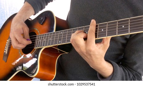 Guitarist performance barre on acoustic guitar correctly clamp chord etalon game mediator close-up blurred background