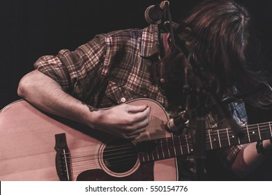 Guitarist performing on stage with acoustic guitar. Man with long hair playing guitar with hair over his face.