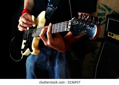 Guitarist play rock guitar. White electric guitar
