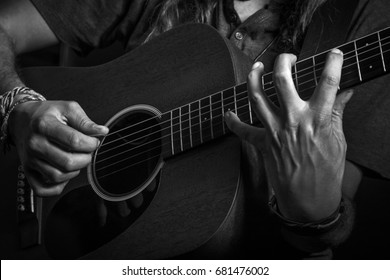 Guitarist playing acoustic guitar in studio photography black and white