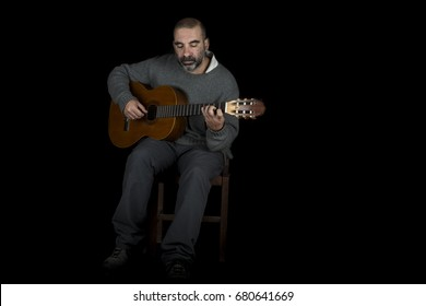 guitarist playing his instrument on black background