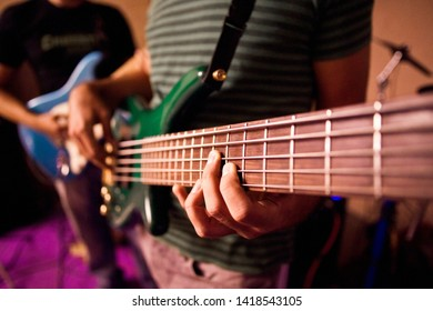 Guitarist playing the notes of a bass during a rehearsal, close-up.