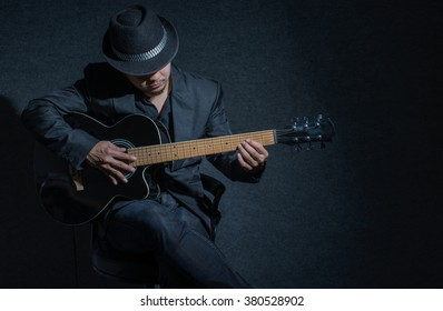 Guitarist playing on dark.lowkey image
