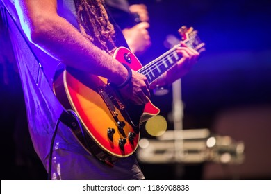 Guitarist playing on electric bass guitar on stage. Colorful, soft focus and blur background.