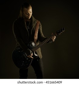 Guitarist playing rock music. On dark background. Beautiful guitar.