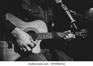 The guitarist plays an acoustic guitar with a capo in front of a microphone. The concept of music recording, rehearsal or live performance.
