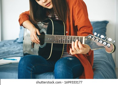 The guitarist plays the guitar. Or a girl learns to play the guitar at home. Home-based individual tuition.