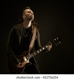 The guitarist plays solo. Close-up. Dark background