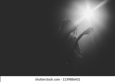 Guitarist silhouette on a stage in a backlights playing rock solo.