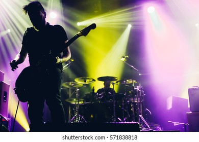 Guitarist silhouette on a stage in a backlights with the drummer background