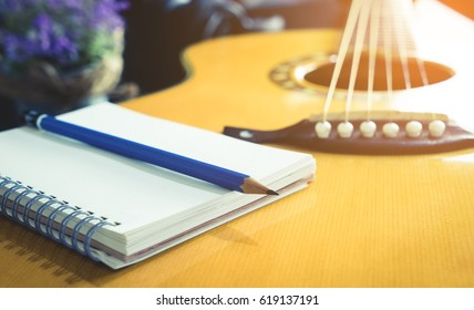 Guitarist Songwriter with blank notebook and pencil on Acoustic guitar for Folk country song music writing concept.