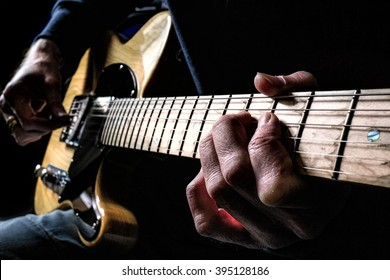 Guitarist strumming a guitar late at night in a dark room writing songs.