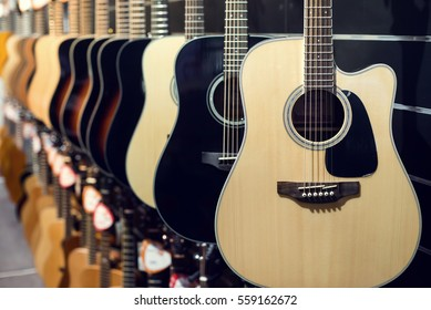 Guitars a row in the store background.