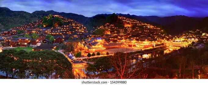 GUIZHOU, CHINA - APRIL 17: Xijiang miao village, largest village in Guizhou Miao ethnic minority, April 17, 2010. Night illumination of houses and bridge over river village in Xijiang. Leishan County.