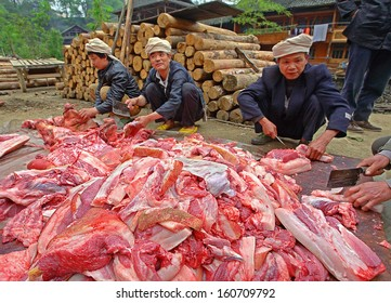 GUIZHOU PROVINCE, CHINA - APRIL 12: Chinese farmers butchering pork on road in middle of rural street, April 12, 2010. Asian pork, Chinese peasants  butchering swine carcasses in the village street.