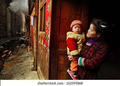 GUIZHOU PROVINCE, CHINA - APRIL 13:  Chinese woman with child in her arms, stands on village street, near wooden house, April 13, 2010. Asian family from rural areas, mother holding son in her arms.