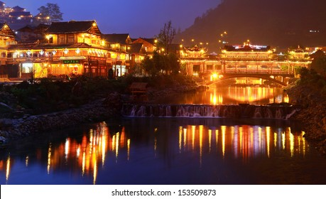 GUIZHOU PROVINCE, CHINA - APRIL 18: Xijiang miao village, the largest village in Guizhou Miao ethnic minority, April 18, 2010. Night illumination of houses and a bridge over a river village in Xijiang