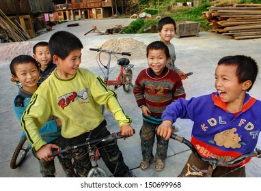 GUIZHOU PROVINCE, CHINA - APRIL 8: Unidentified Chinese boys sit on the bikes and laugh, April 8, 2010. Zhaoxing village, Liping County. Chinese village, rural life in China. Dong ethnic Minorities village.