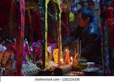 GUIZHOU PROVINCE, CHINA – CIRCA DECEMBER 2018: A man standing in front of colorful altar made in occasion the ritual redeeming the vow. Translation of text: worship nature and ancestors.