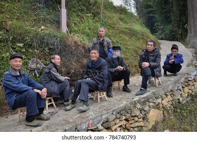 GUIZHOU PROVINCE, CHINA – CIRCA DECEMBER 2017:  Several old men sit together in the narrow pathway.