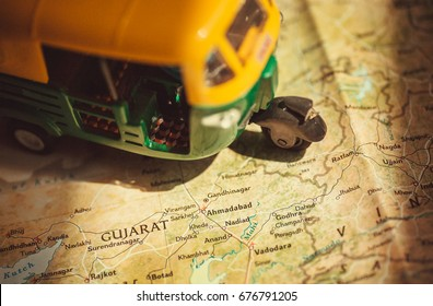Gujarat on India roads map with driving toy model of auto-rickshaw vehicle.
