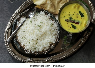 Gujarati Kadhi served with rice and Papad - Indian vegetarian curry made of buttermilk and Chick pea flour