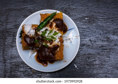 Gujarati khaman Dhokla made with chana dal served with coconut and chutni on a white plate and black background. Selective focus. - Shutterstock ID 1973992928