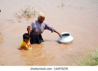 GUJRANWALA, PAKISTAN - AUG 24: Flood affected woman with her child pass through flood water at a flood hit area in Mianwali Hafizabad District on August 24, 2012 in Gujranwala, Pakistan.