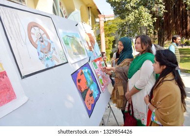GUJRANWALA, PAKISTAN - MAR 04: Visitors take keen interest in painting during exhibition in favor of Pakistan Armed Forces organized by Arts Council on March 04, 2019 in Gujranwala.