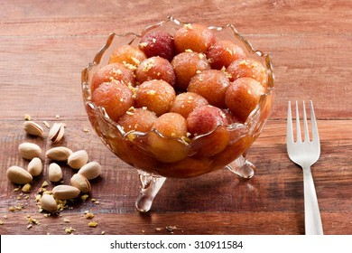 Gulab Jamun in a glass bowl on wood background with pista