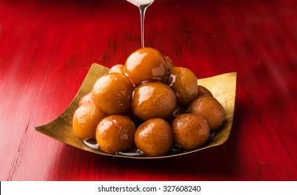 Gulab Jamun served in a square brass plate with pouring sweet syrup - An Indian sweet dish