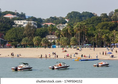 Gulangyu, Fujian Province / China - Dec 2, 2015: Sand beach on Gulangyu Island. With motorboats & tourists. In the background residential buildings. The whole island is an UNESCO World Heritage Site