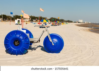 Gulf coast beach in Biloxi, Mississippi with water tricycles and lounge chairs.