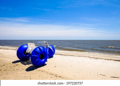 Gulf coast beach in Biloxi, Mississippi with water tricycle along the shoreline.
