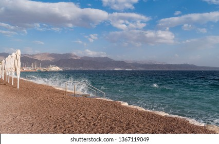 the gulf of eilat akaba on the red sea showing a resort beach with cruise ships and the mountains of jordan in the background
