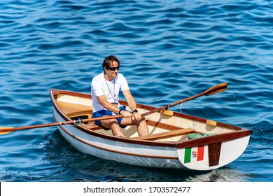 GULF OF LA SPEZIA, LIGURIA, ITALY - JULY 21th, 2019: A man on a small wooden rowboat in the blue Mediterranean sea in front of the ancient Tellaro village, Liguria, Italy, Europe