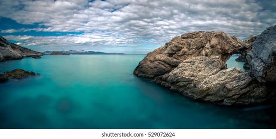 Gulf of Mirambello with clouds, calm sea and a sone arch at the right of te rock, Crete, Greece.