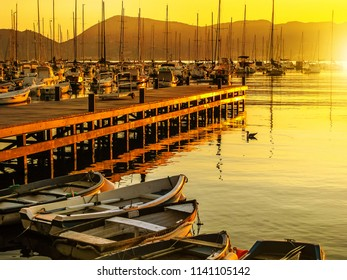 Gulf of Poets of Lerici town in La Spezia province at sunset. Sailing boats and motor boats in the twilight sun in Ligurian Coast, Italy. Scenic Lerici Port with wooden jetty.