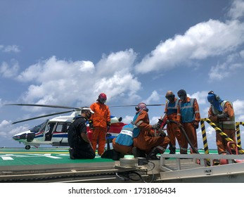 Gulf of Thailand, Thailand- May 7,2020 : helicopter on refueling offshore Helicopter officer working on offshore helipad or The helicopter landing officer (HLO) is on the oil rig platform in the gulf