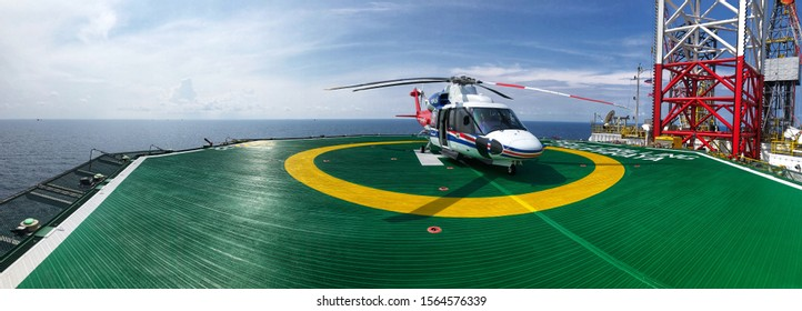 Gulf of Thailand, Thailand, November 19,2019: Offshore transport helicopter on helideck or helipad waiting for passenger to board the aircraft, traveling, air transportation panorama picture