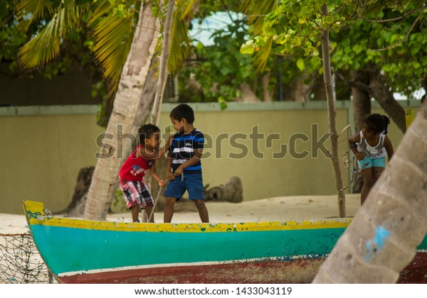 Gulhi, Maldives; September 14 2017: Children playing on a wooden boat in the sand on the island of Gulhi, Maldives.