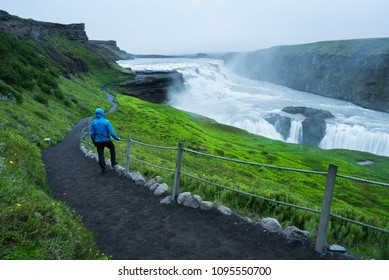 Gullfoss - most beautiful waterfall in Iceland. Golden Ring Tourist Attraction. Man in blue jacket near the cascade. Beauty in nature