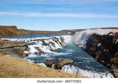 Gullfoss waterfall, popular destination of the golden circle route in southwest Iceland, with foreground of dry grass on sunny day with white cloud on blue sky and rainbow over the turquoise water.