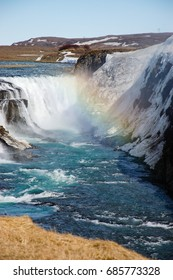 Gullfoss waterfall, popular destination of the golden circle route in southwest Iceland, with foreground of dry grass on sunny day with blue sky and rainbow above the turquoise water in portrait view.